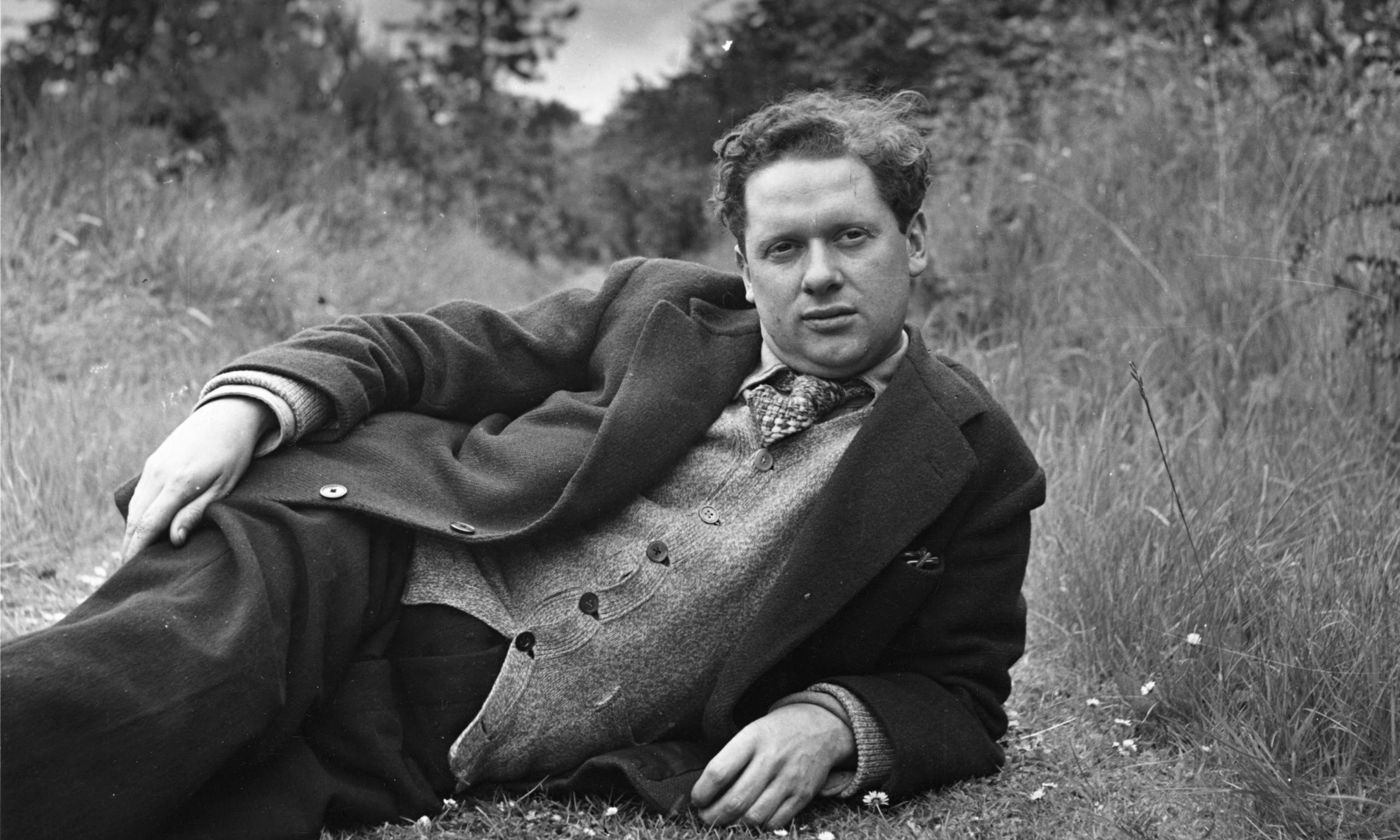 A photograph of the poet Dylan Thomas reclining in a meadow