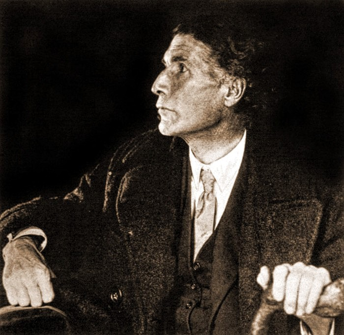A half-length tinted monochrome photograph of the writer John Cowper Powys